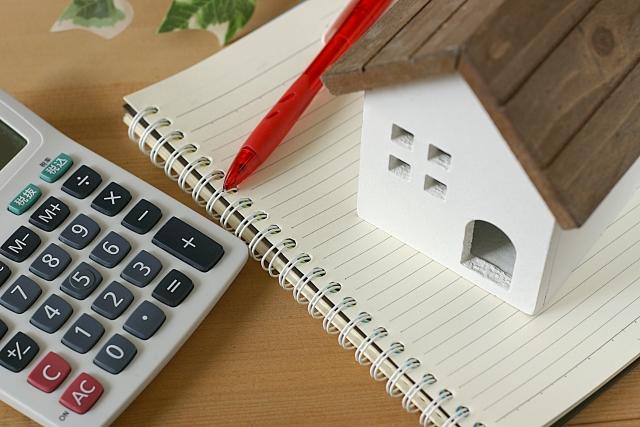 ノートと電卓と家の模型